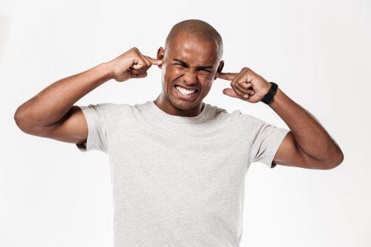 Homem negro tampando os ouvidos para que o barulho no condomínio o incomode menos.