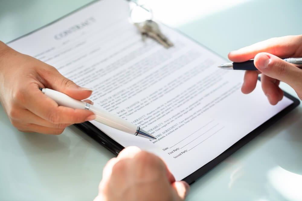 Assinatura de contrato representando os documentos de responsabilidade do fiador em contrato de locação