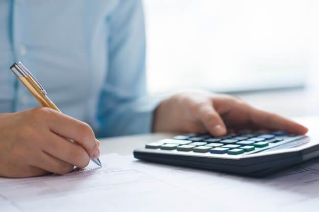 Imagem mostrando as mãos de uma pessoa que está usando uma calculadora para confirmar o valor da multa de rescisão de contrato de aluguel.